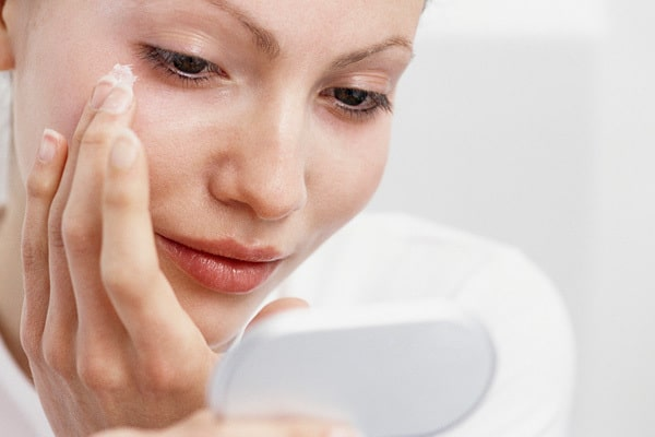 Woman-applying-facial-lotion